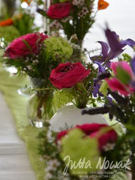 Tischdeko Jutta Nowak: Fläschchenreihe mit bunten Frühlingsblumen